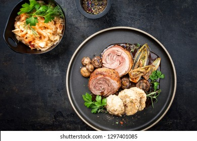 Traditional rolled boar roast with dumpling, fried vegetable and mushroom as top view on a modern design plate with game red wine sauce