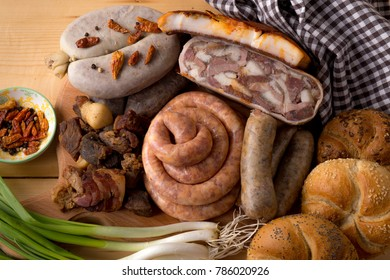 Traditional romanian meat and sausages selection with spices, green onions and bread buns on wooden table background
