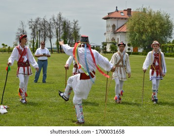 """Traditional Romanian Whitsuntide dance - """"Calus"""" or """"Calusarii"""" dance event with men dressed in colorful clothes after Easter - Dragasani, Dolj / Romania - 5/28/2018"""