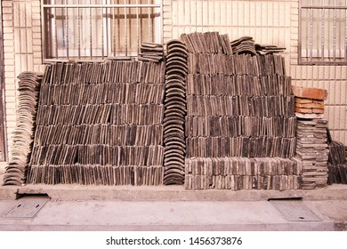 Traditional roofing tiles stacked neatly against a wall