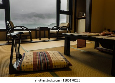 Traditional room in a ryokan - Japanese hotel, with low chairs and tables in the front of the picture and window in the background. Misty mountains are the view from the window.