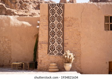 "Traditional Rug and a Wicker Floor for Serving Food Hanging on an Old Mud Wall in ""Al Ola"" Al Ula, Saudi Arabia. Al Ola is Part of Madinah Province in Western Saudi Arabia"