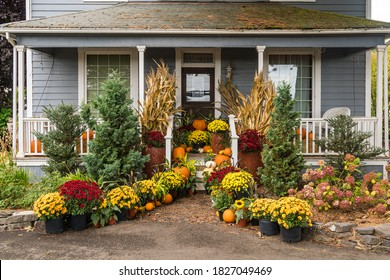 Traditional Rural Farm House decorated for autumn, fall flowers and pumpkins.