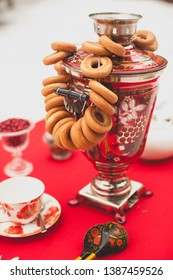 Traditional Russian brass painted samovar on a red tablecloth, a symbol of hospitality. Crispy bagels, drying or bagels hang on the samovar. Blurred background.