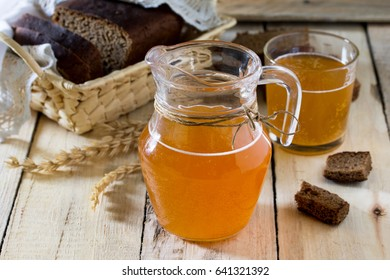 Traditional Russian cold rye drink Kvas in a glass and a jug on the kitchen table in a rustic style. Kvass from bread, rye malt, sugar and water. Copy space.