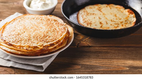 Traditional Russian Crepes Blini stacked in a plate and pancake in a cast-iron frying pan on dark wooden table. Maslenitsa traditional Russian festival meal. Russian food, russian kitchen