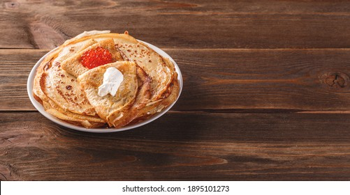 Traditional Russian Crepes Blini stacked in a plate with red caviar, fresh sour creamon dark wooden table. Maslenitsa traditional Russian festival meal. Long wide banner. Space for text