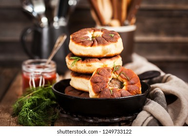 Traditional Russian deep fried meat patties (belyash) on rustic background