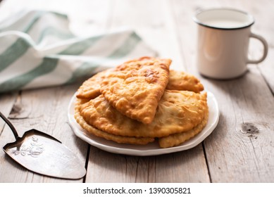 Traditional Russian deep fried meat pies - chebureki on a white plate and gray wooden background