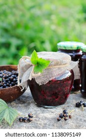 Traditional Russian dessert. Blackcurrants varenie or jam in a glass jar in rustic style - Shutterstock ID 1138095149