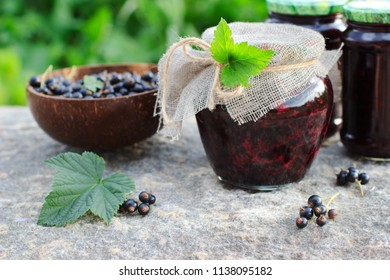 Traditional Russian dessert. Blackcurrants varenie or jam in a glass jar in rustic style - Shutterstock ID 1138095182