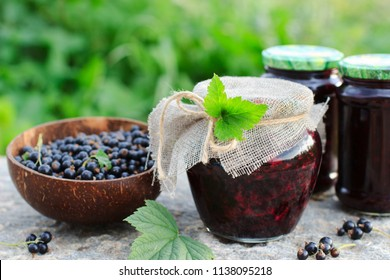Traditional Russian dessert. Blackcurrants varenie or jam in a glass jar in rustic style - Shutterstock ID 1138095218