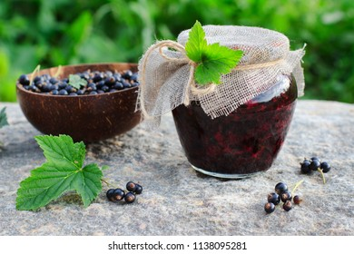 Traditional Russian dessert. Blackcurrants varenie or jam in a glass jar in rustic style - Shutterstock ID 1138095281