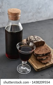 Traditional Russian drink kvass made from bread, rye malt, sugar and water. Kvass in bottle with rye bread and glass on a gray background.