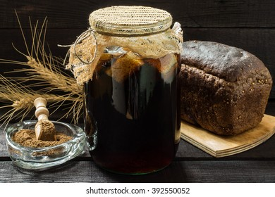 Traditional Russian drink kvass made from bread, rye malt, sugar and water. Kvass in the jug, rye bread and malt in a bowl with scoop on a dark wooden background. Selective focus