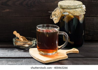 Traditional Russian drink kvass made from bread, rye malt, sugar and water. Kvass in the jar, rye malt in a bowl with scoop on a dark wooden background. Selective focus