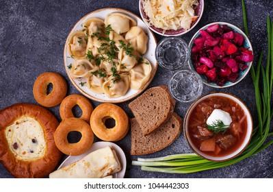 Traditional Russian food. Borscht, pelmeni, vinaigrette sauerkraut vodka and sweets