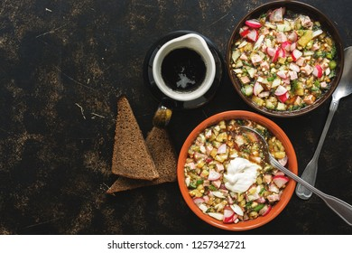 Traditional Russian food okroshka with kvass and rye bread on a dark background. Top view, copy space