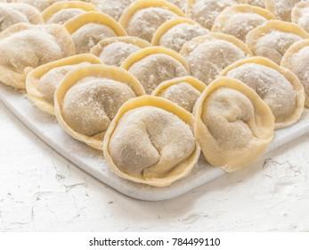 Traditional Russian handmade dumplings frozen on the board. Russian pelmeni. Ravioli