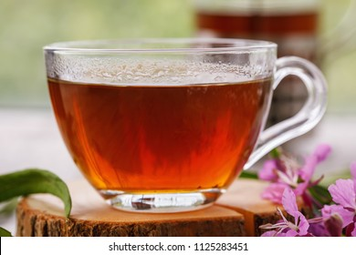 Traditional Russian herbal drink Ivan-tea in a transparent cup close-up on a wooden table
