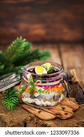 Traditional Russian layered betroot and herring salad (under a fur coat) in glass jar, rustic wooden background, selective focus