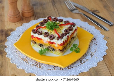 Traditional Russian layered salad Mimosa composed of canned fish covered with layers of boiled potato, carrot, onion, cheese, eggs and mayonnaise.