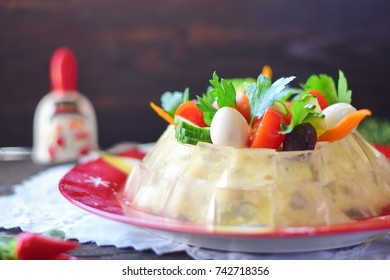 Traditional Russian meat salad with a jelly cubes coat, decorated with quail eggs, cherry tomatoes, cucumbers, paprika, olives and parsley on a Christmas traditional plate