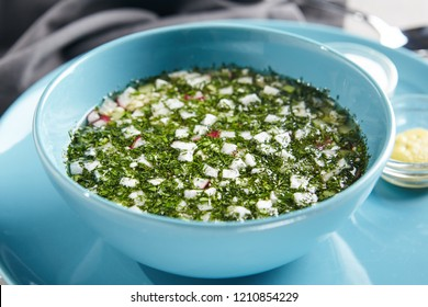 Traditional Russian Okroshka Made of Diced Cucumbers, Radishes, Spring Onions, Boiled Potatoes, Eggs, Cooked Meat, Finely Chopped Greens and Kvass. Summer Cold Soup in Blue Bowl