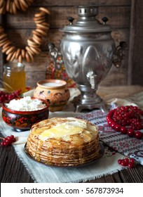 Traditional russian pancakes with cottage cheese, milk, butter and sour cream on napkins with embroidery. Traditional dishes on the holiday Carnival Shrovetide