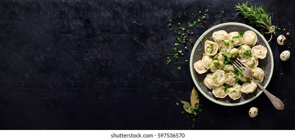 Traditional russian pelmeni, ravioli, dumplings with meat on black concrete background. Parsley, quail eggs, pepper, rosemary, bay leaf and spices. Top view. Copyspace. Banner