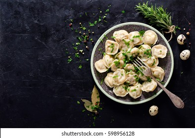 Traditional russian pelmeni, ravioli, dumplings with meat on black concrete background. Parsley, quail eggs, pepper, rosemary, bay leaf and spices. Top view. Copyspace