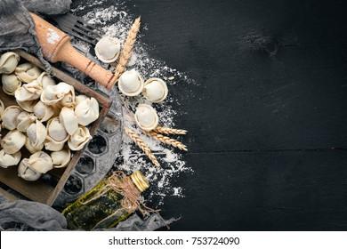 Traditional russian pelmeni, ravioli, dumplings with meat on black concrete background. Top view. Copyspace.