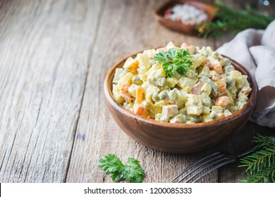 Traditional Russian salad with cooked vegetables with mayonnaise in a bowl. Wooden background.