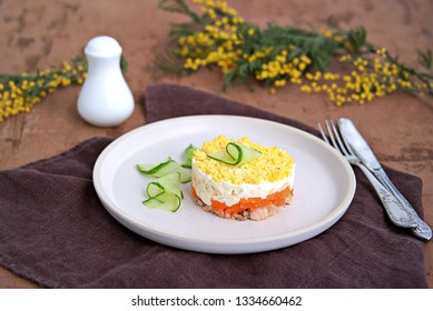 Traditional Russian salad Mimosa with boiled pink salmon, carrots, onions and eggs on a brown concrete background. Served on ceramic plates, decorated with sliced fresh cucumber.