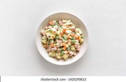 """Traditional russian salad """"Olivier"""" from boiled vegetables and sausage with mayonnaise in bowl. Russian New Year or Christmas salad on light background with copy space. Top view, flat lay"""
