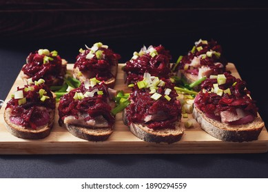Traditional russian sandwiches with spicy beetroot salad, pickled onions and smoked herring. Bruschettas with beetroot and herring. Herring under a fur coat. Black background. Wooden cutting board.