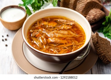 Traditional Russian sauerkraut soup Shchi in bowl on rustic wooden background. Selective focus.