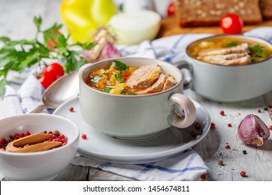 Traditional Russian soup with cabbage, vegetables and meat in a ceramic bowl on a white wooden table, selective focus.