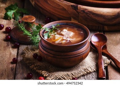 Traditional Russian soup from sauerkraut, meat and potatoes in a clay pot, vintage wood background, rustic style, selective focus