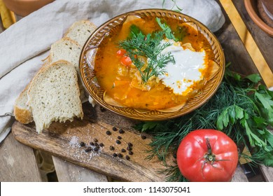Traditional Russian sour cabbage soup (shchi) with sour cream and herbs on a wooden table with bread, pepper and parsley, on a linen tablecloth. Top view. Vertical