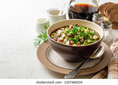 Traditional Russian summer cold soup okroshka with kvass in bowl on white concrete background. Selective focus.