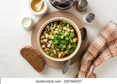 Traditional Russian summer cold soup okroshka with kvass in bowl on white concrete background. Top view.