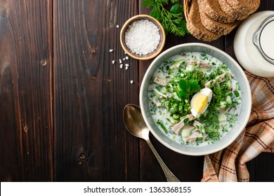 Traditional Russian summer cold soup okroshka with kefir in bowl on dark wooden background. Top view. Copy space.