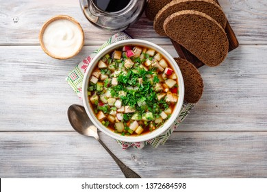 Traditional Russian summer cold soup okroshka with kvass in bowl on wooden background. Top view.