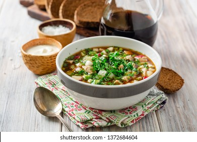 Traditional Russian summer cold soup okroshka with kvass in bowl on wooden background. Selective focus.