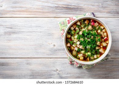 Traditional Russian summer cold soup okroshka with kvass in bowl on wooden background. Top view. Copy space.