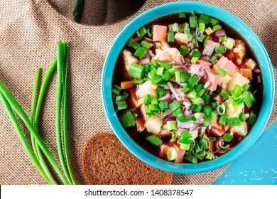 Traditional Russian summer cold soup okroshka with kvass in bowl on blue wooden background. Close up. Selective focus.