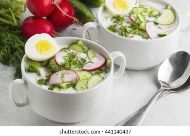 Traditional Russian summer cold soup - okroshka with garden radish, cucumber, kefir (yogurt), fennel on a white background