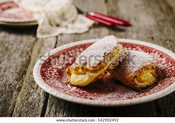 Traditional Russian sweet pies of short pastry with curd sprinkled with powdered sugar on a bright painted plate on a dark shabby wooden background. Selective focus. Toned image