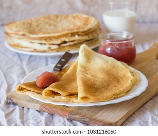 Traditional Russian sweet thin pancakes with jam on a white plate and light background. Homemade breakfast.